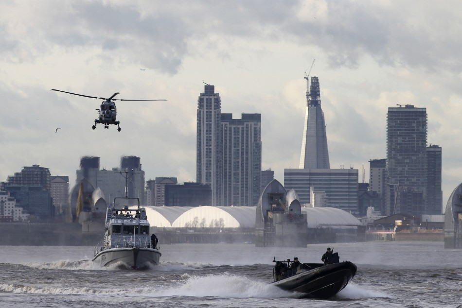 A helicopter watches over two boats