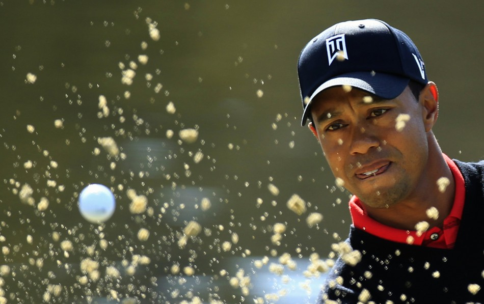 Woods of the U.S. hits out of a bunker onto the third green during the final round of the Chevron World Challenge PGA golf tournament in Thousand Oak