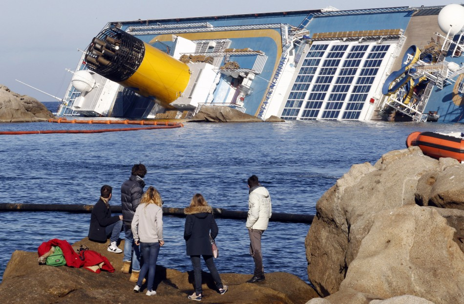 People look from a rock in front of the Costa Concordia cruise ship which ran aground off the west coast of Italy
