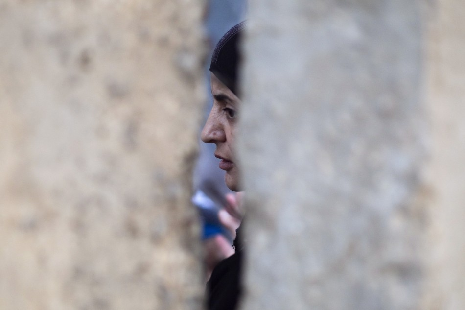 A Palestinian woman waits behind a wall