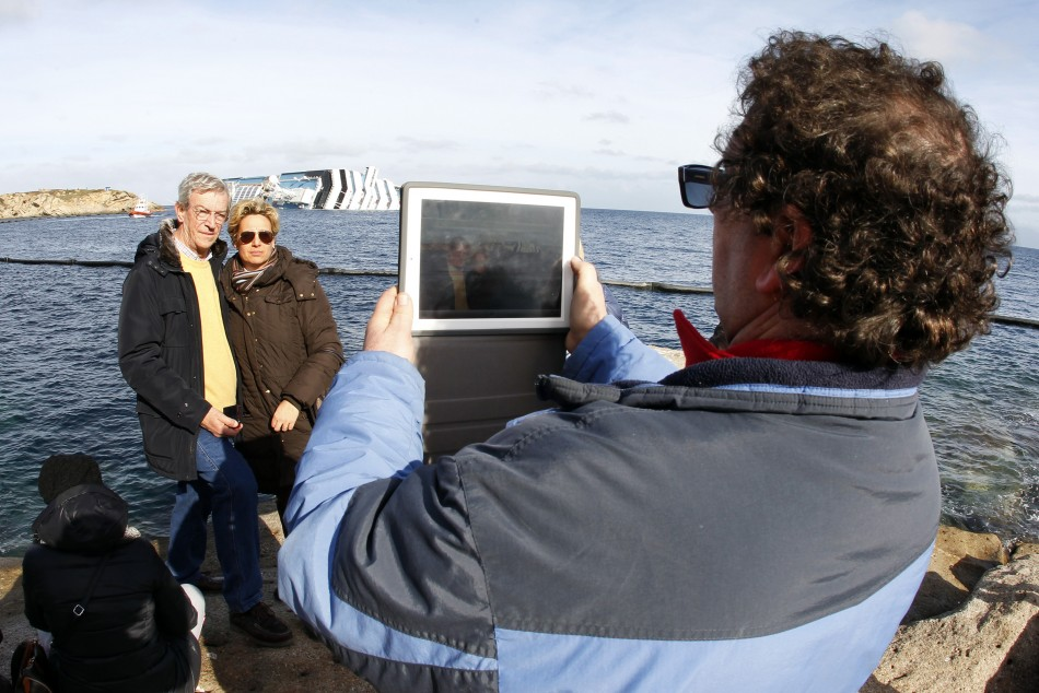 People take a picture on a rock in front of the Costa Concordia cruise ship which ran aground off the west coast of Italy