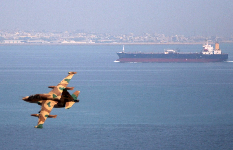 Iranian military fighter plane flies past oil tanker during naval manoeuvres in Persian Gulf and Sea of Oman
