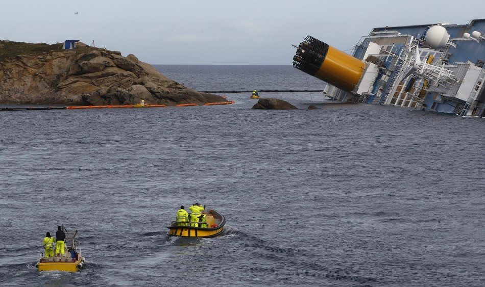 Oil recovery workers pass next to the Costa Concordia cruise ship which ran aground off the west coast of Italy