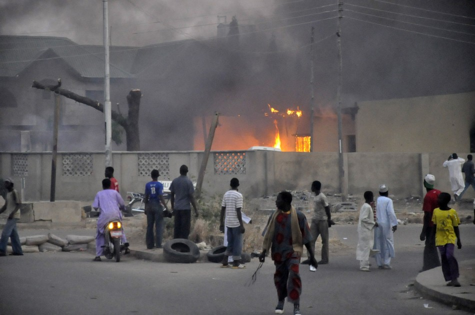 People surround a burning car after Boko Haram attacked a police station in Kano