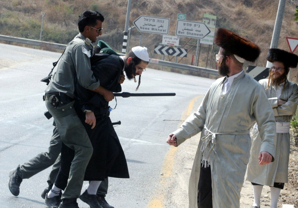 An Israeli border police officers detains an Ultra-Orthodox Jewish man