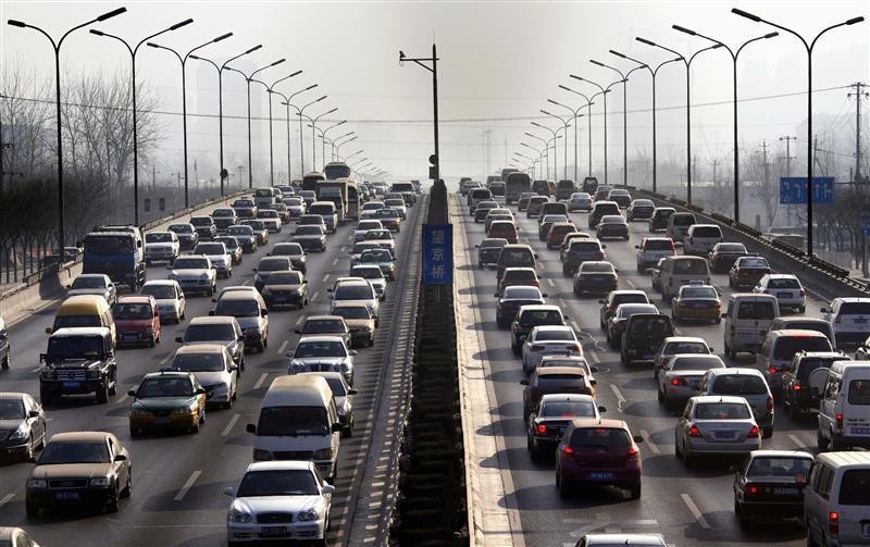 Cars drive along a main road in central Beijing