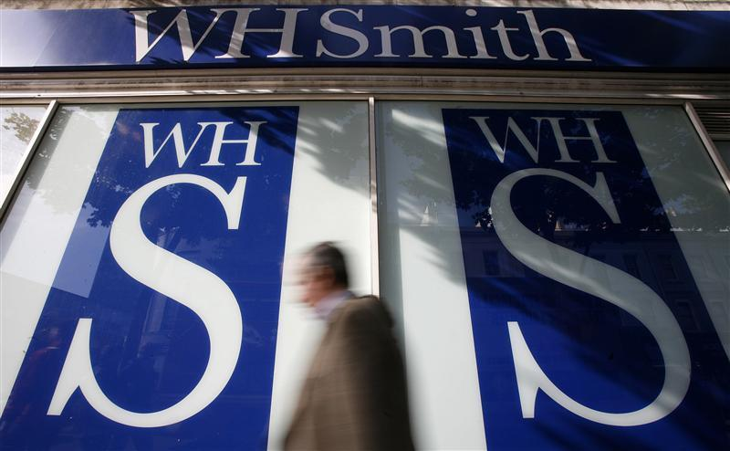 Pedestrians walk past a WH Smith shop in London