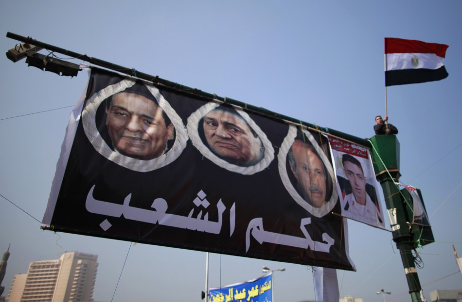 A demonstrator waves an Egyptian flag next a poster of former President Hosni Mubarak and Field Marshal Mohamed Hussein Tantawi during a protest marking the first anniversary of Egypt's uprising at Tahrir square, in Cairo