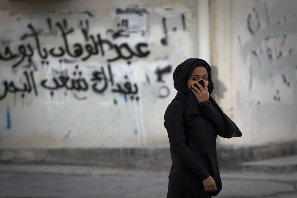 A woman covers her face during a standoff with police after a mourning procession on the third day after the death of Yassin Al-Afsoor in the village of Mameer