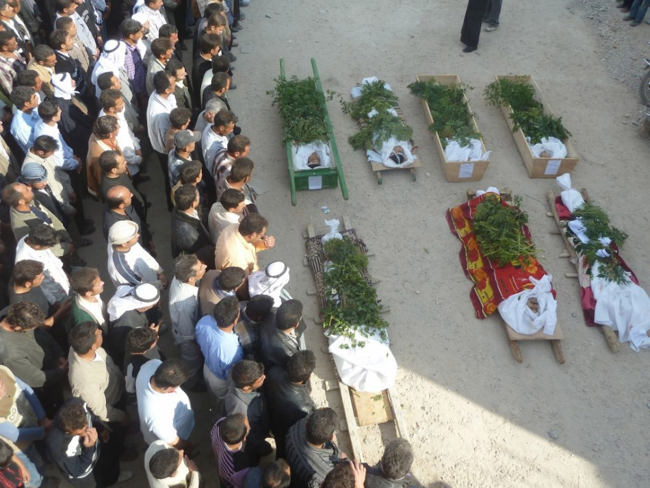 Anti-government protesters pray bodies comrades killed Homs