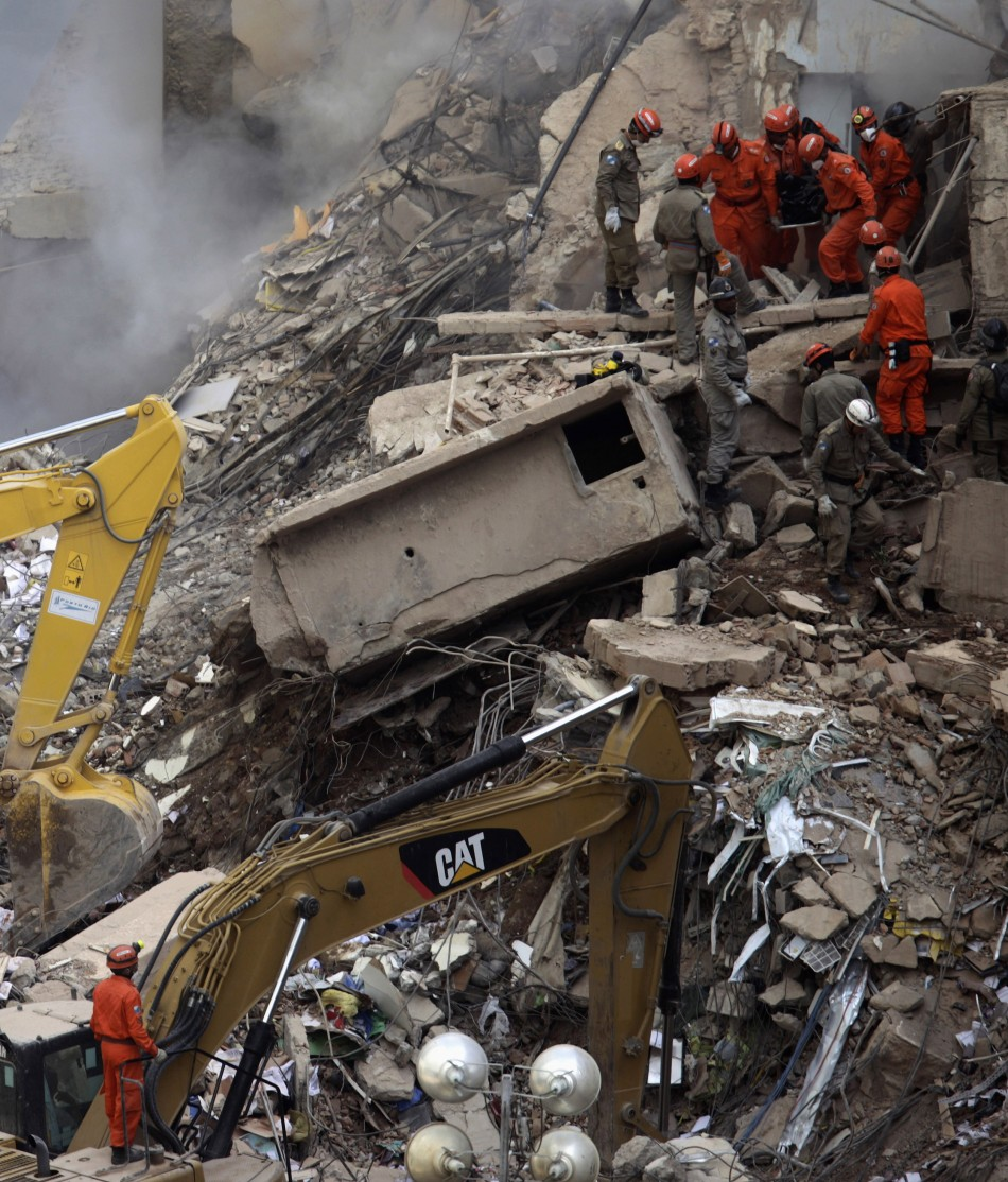 Firefighters carry the body of a victim among the debris of a collapsed building in Rio de Janeiro