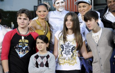 Michael Jacksons children Prince, Blanket, Paris and singer Justin Bieber pose for photographs at a ceremony where Jackson is immortalized with hand and foot imprints in cement in the courtyard of Hollywoods Graumans Chinese Theatre