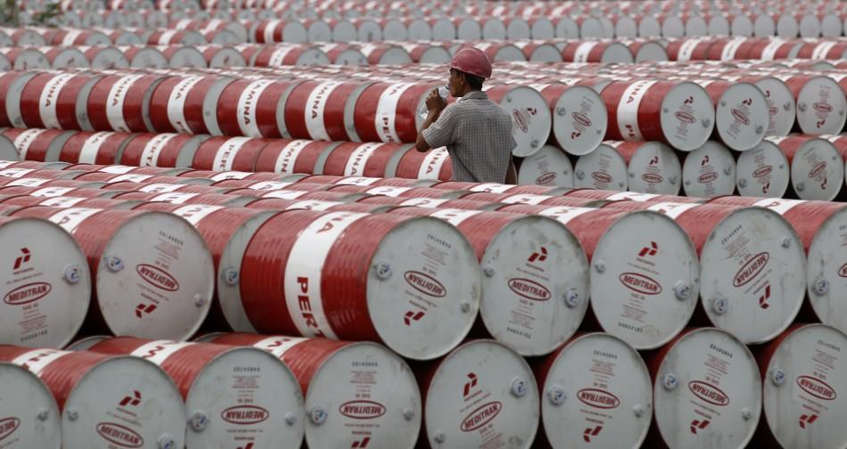 A worker walks in between oil barrels at Pertamina's storage depot in Jakarta, Indonesia, on Jan. 26, 2011.