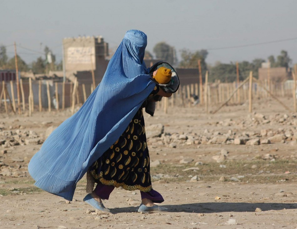 A woman clad in a burqa in Afghanistan with her child