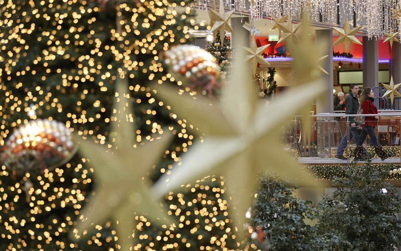 Shoppers walk among illuminated Christmas decorations in a shopping mall at Berlin's Potsdamer Platz