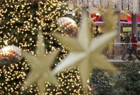 Shoppers walk among illuminated Christmas decorations in a shopping mall at Berlin's Potsdamer Platz