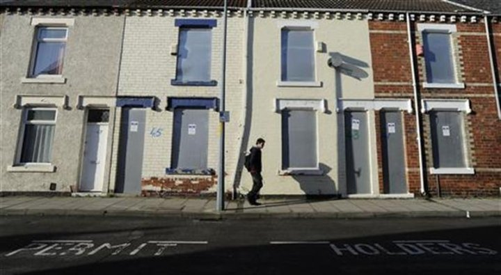 A pedestrian walks past boarded up houses on Coral Street in Middlesbrough, northern England