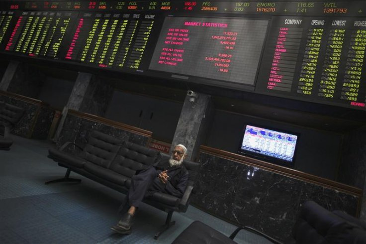Trader sits on couch underneath an electronic board displaying share prices at Karachi Stock Exchange