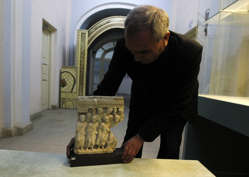 An Afghan specialist displays an ancient pre-Islamic sculpture that was returned to Afghanistan at the Afghan National Museum in Kabu