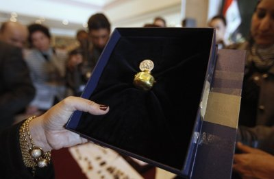 An employee displays a recovered tiny gold jar, dating to 4,500 BC at the Iraqi Ministry of Foreign Affairs headquarters in Baghdad