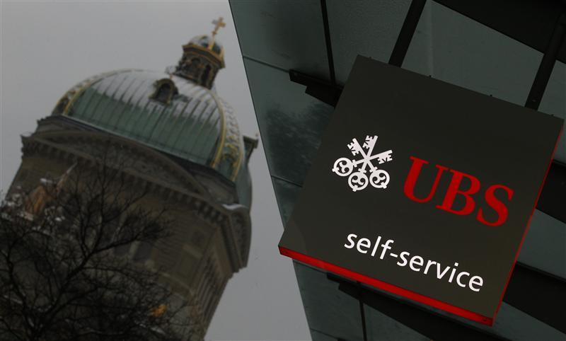 A UBS logo is pictured on a UBS bank building in front of the Swiss federal parliament building in Bern