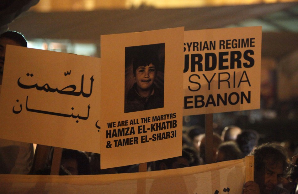 Protesters carry placards and poster of Syrian child Hamza al-Khatib shout anti-Syrian regime slogans