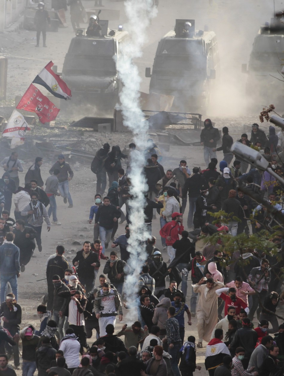 Protesters run from tear gas thrown by police forces during clashes near the Interior Ministry in Cairo