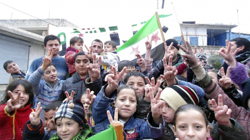 Children flash victory signs during a rally against Syria's President Bashar al-Assad in Jerjenaz, near Idlib