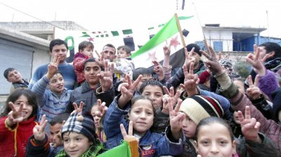 Children flash victory signs during a rally against Syrias President Bashar al-Assad in Jerjenaz, near Idlib