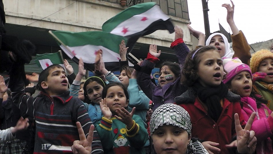 Children chant slogans as Syrian independence flags are waved behind them during a protest against Syrias President Bashar al-Assad in Khalidieh, near Homs