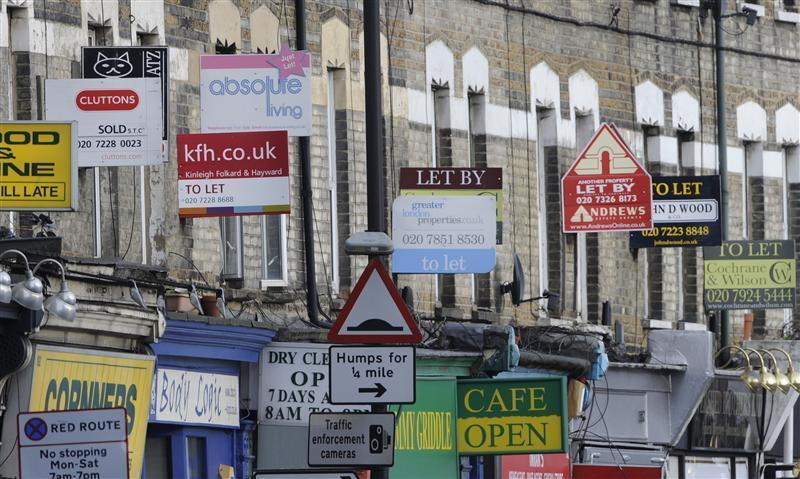 Property letting and sale signs are seen above shops in south London