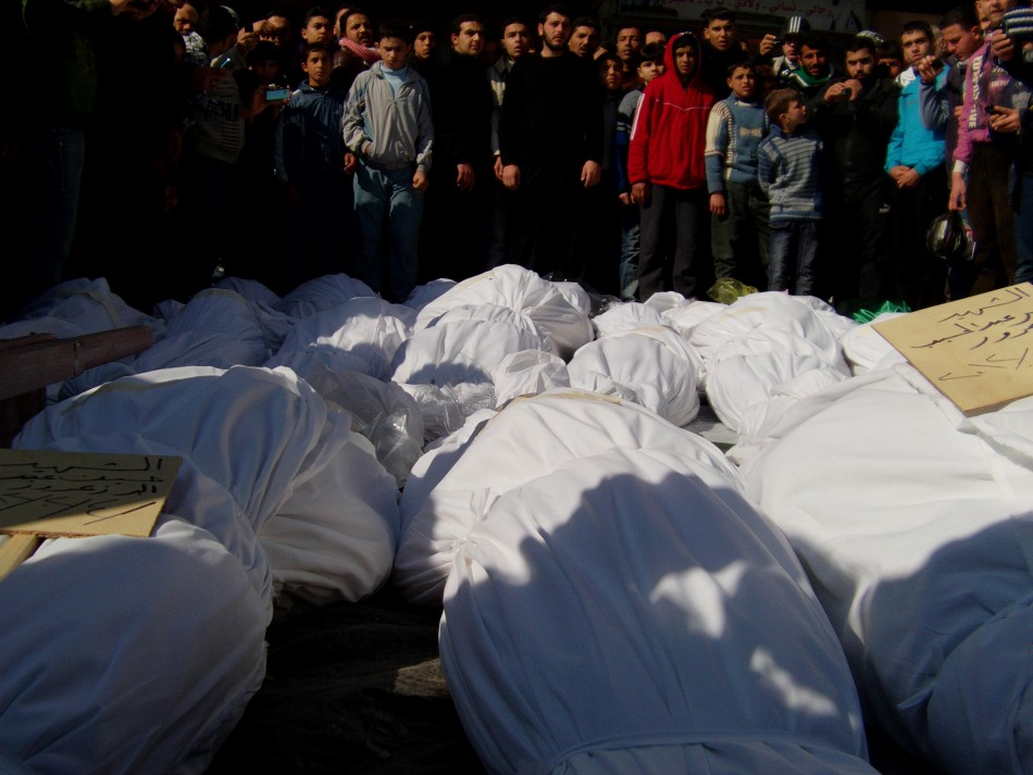 Residents attend a burial ceremony for what activists say are victims of shelling by the Syrian army