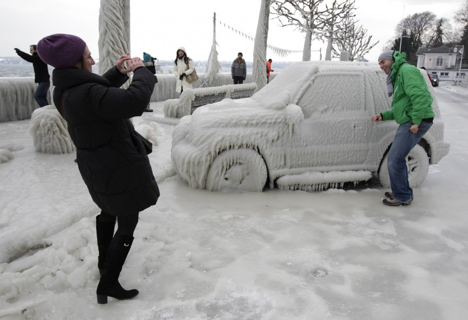 A woman takes a picture of a man near an ice covered car in Versoix near Geneva