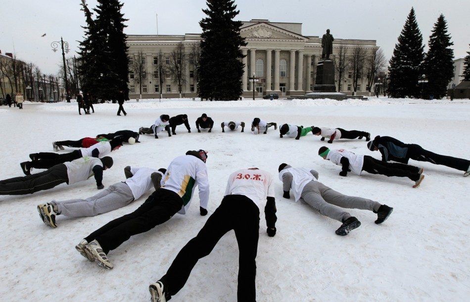 Belarusian men do physical exercises at the main square of the town of Molodechno