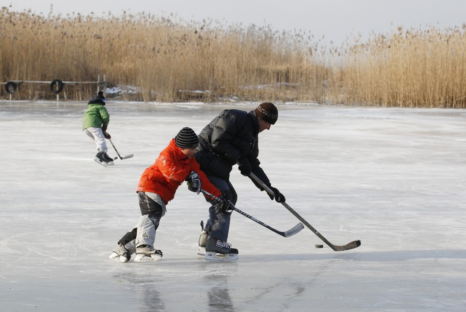 People play ice hockey on a frozen part of the lake Neuchatel in Cudrefin