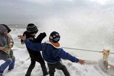 Children play as waves hit the frozen shore in the Black Sea harbour of Constanta