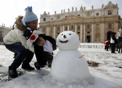 A mother with her son look at a snowman at San Peter square in Vatican