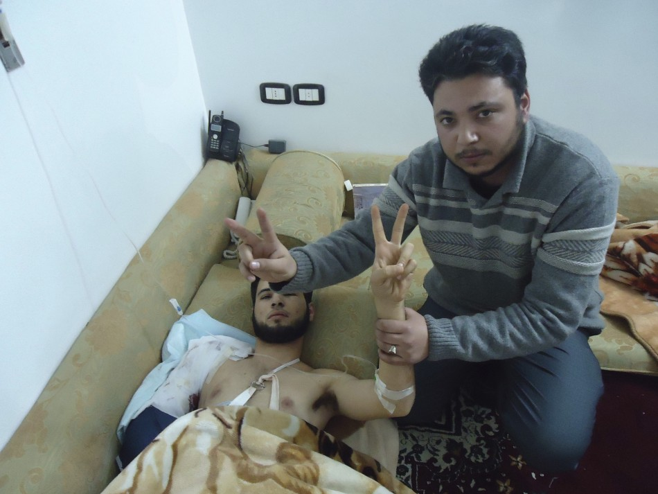 A man flashes a victory sign and holds up the arm of a man wounded on February 5, 2012, also flashing a victory sign, in Baba Amro, a neighbourhood of Homs