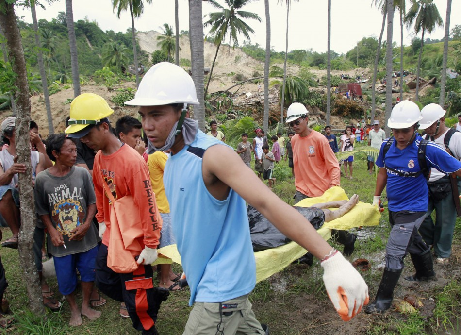 Rescuers carry a body retrieved from a landslide