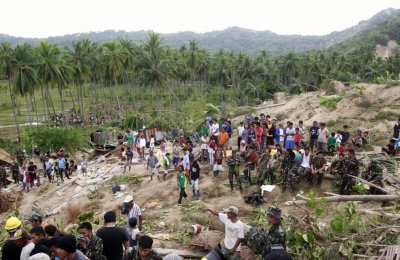 Residents and soldiers gather at the site of a landslide