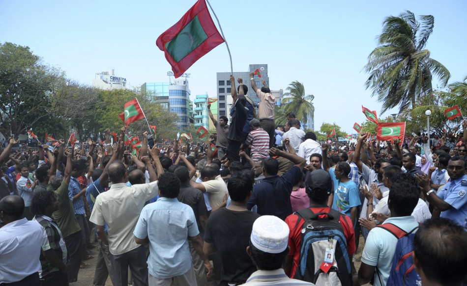 Supporters of opposition parties hold Maldives national flags as they celebrate after Maldives President Nasheed resigned in Male