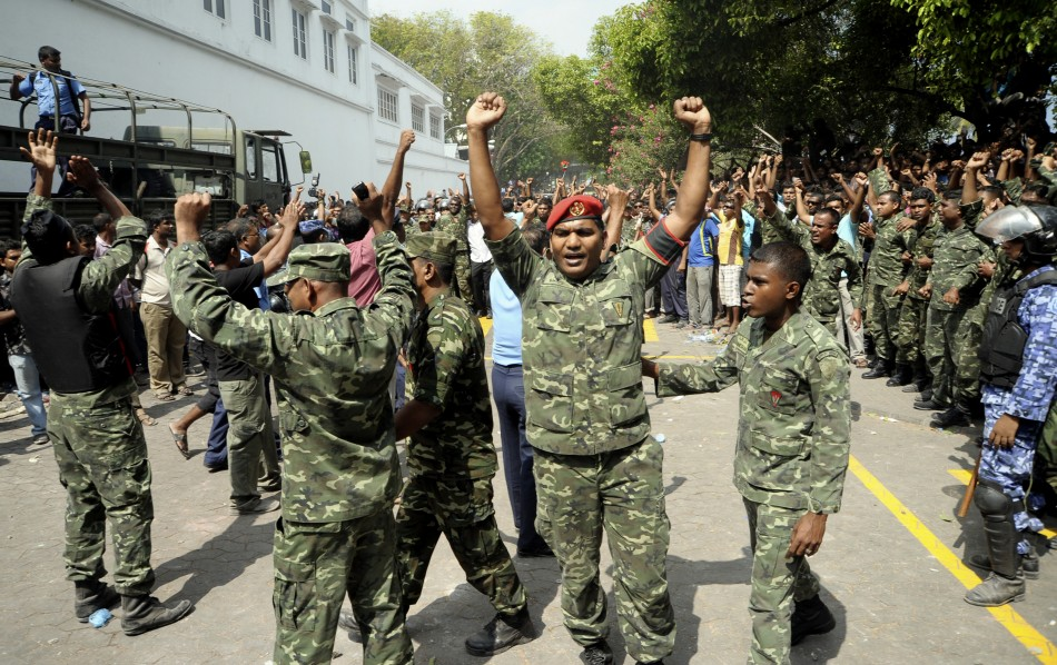 Maldives soldiers raise their hands and shout slogans in Male