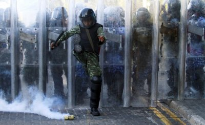 An army officer kicks a tear gas cannister during a clash with the supporters of ousted Maldivian president Mohamed Nasheed in Male