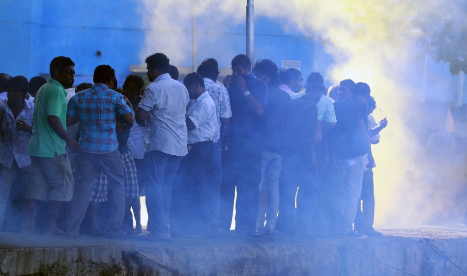 Supporters of ousted Maldivian President Nasheed take cover from tear gas and smoke during a clash in Male