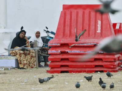 Women sit next to plastic barriers used during Tuesdays protests in Male