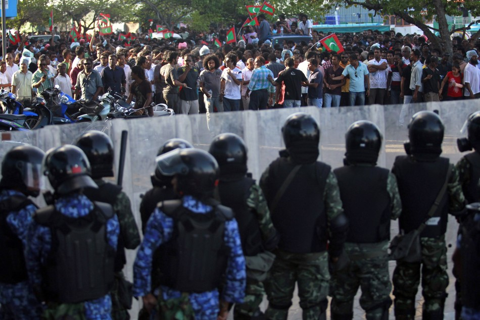 Maldivian riot police officers stand guard as they block supporters of the ousted Maldivian president Mohamed Nasheed during a clash in Male
