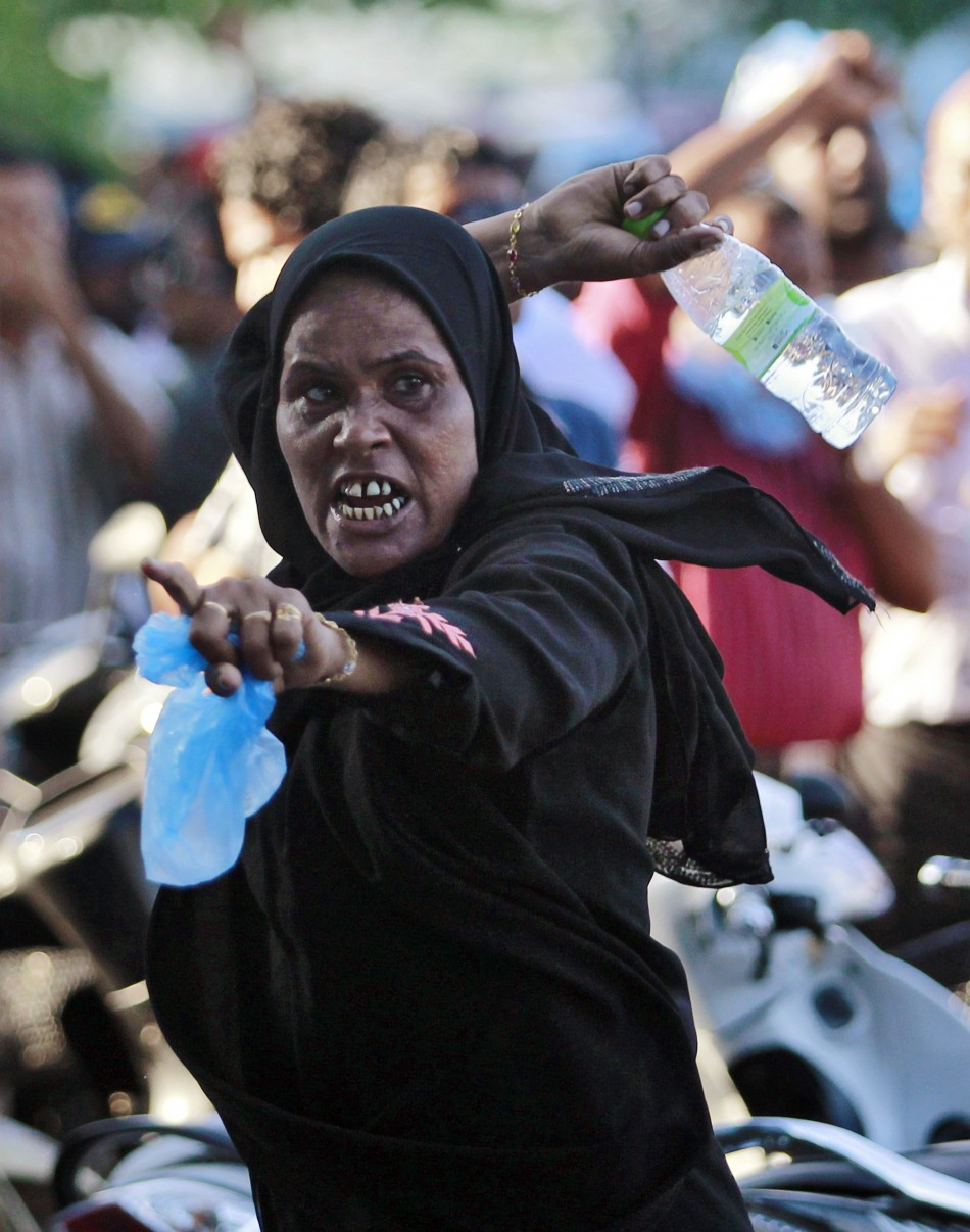 A supporter of ousted Maldivian president Nasheed throws a bottle at riot police officers during a clash in Male