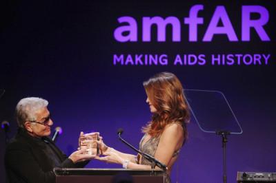 Model Cindy Crawford R hands an award to designer Roberto Cavalli