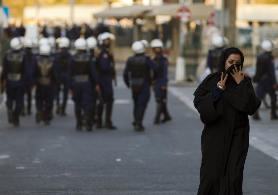 A protester gestures at the camera after passing a police patrol in Manama