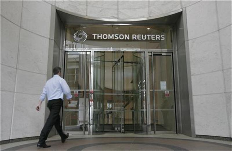 A worker enters the Thomson Reuters building in the Canary Wharf financial district of London